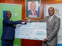 KCB Bank Chief Operating Officer, Samuel Makome hands over a dummy cheque of Kshs 10 million to CBK Governor, Dr Patrick Njoroge. Photo, supplied