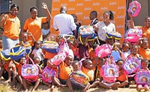 Children at the Siyajabula care facility with female community caregivers celebrate Avon Justine 's good gesture.